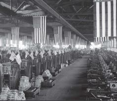 photo of a munitions factory with many flags