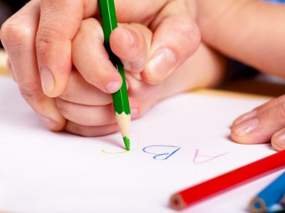 adult and child writing