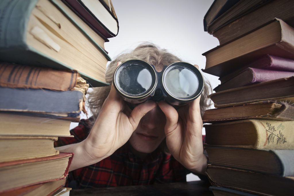 Person with binoculars peering through a stack of books.