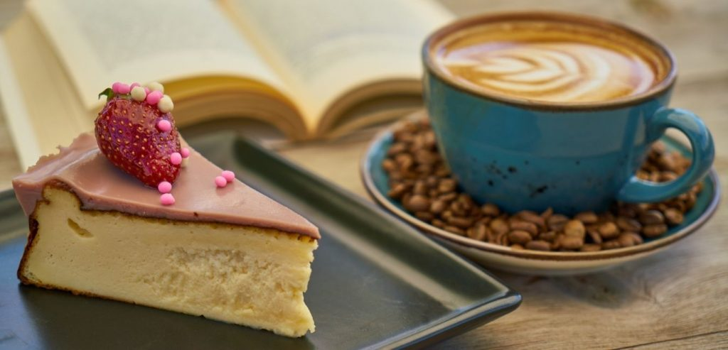open book with a slice of cake and a latte